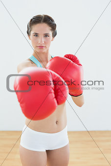 Beautiful woman in red boxing gloves at fitness studio