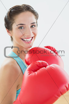 Close up portrait of a beautiful smiling woman in red boxing gloves