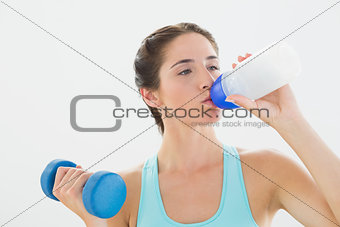 Fit woman with dumbbell drinking water