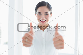 Smiling business woman gesturing thumbs up