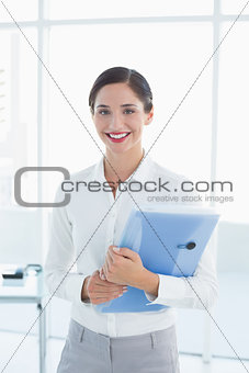 Smiling business woman with folder in office