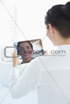 Business woman looking at her reflection in tablet PC