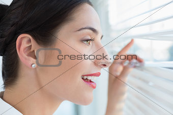 Smiling business woman peeking through blinds at office