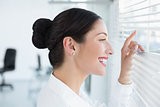 Smiling young business woman peeking through blinds at office