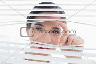 Smiling young business woman peeking through blinds