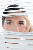 Young business woman peeking through blinds