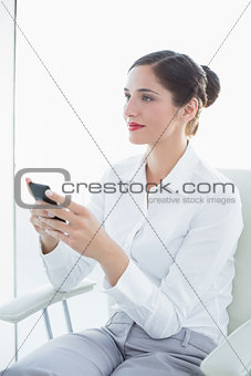 Business woman with mobile phone looking away