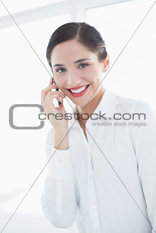 Smiling business woman using mobile phone