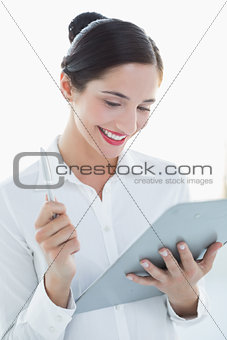 Smiling business woman with clipboard and pen