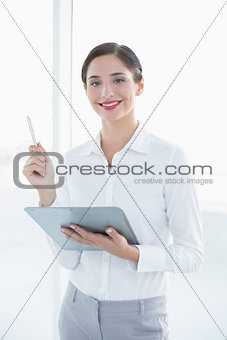 Business woman with clipboard and pen in office