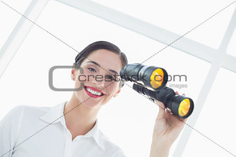 Smiling business woman  with binoculars in office