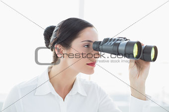 Business woman  looking through binoculars in office