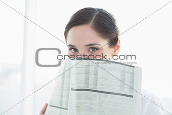 Business woman holding newspaper in front of face