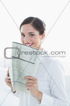 Smiling business woman holding newspaper