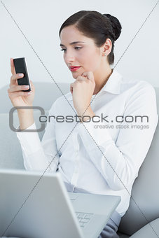 Well dressed woman using cellphone and laptop on sofa