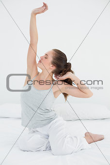 Sleepy woman stretching her arms up