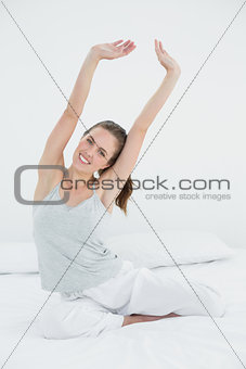 Smiling woman stretching her arms up in bed