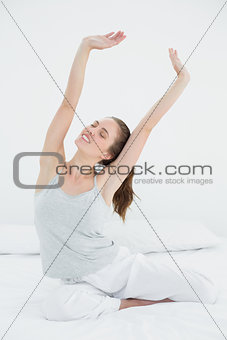 Woman stretching her arms up in bed
