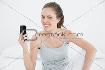 Smiling woman with mobile phone sitting in bed