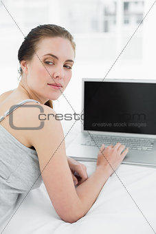 Thoughtful casual woman with laptop in bed