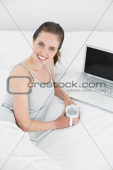 Casual woman with laptop and tea cup in bed