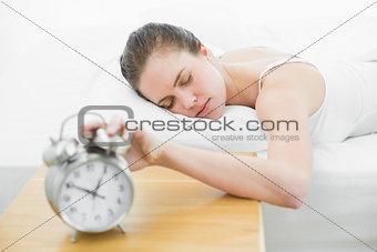 Sleepy woman in bed extending hand to alarm clock