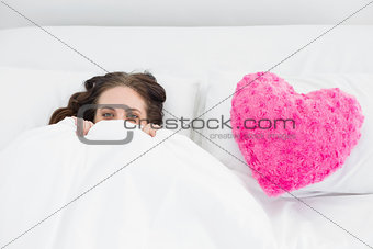 Smiling woman lying in bed with heart  shaped pillow cover