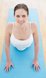 Beautiful smiling woman stretching on exercise mat