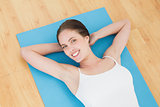 Smiling young woman lying on exercise mat