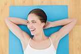 Cheerful woman lying on exercise mat