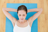 Woman resting on exercise mat with eyes closed