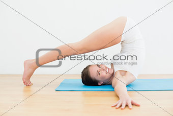 Side view of a smiling woman exercising on mat