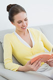 Smiling woman reading a book on sofa