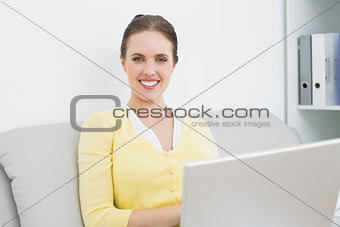 Smiling casual woman with laptop sitting at home