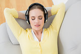 Woman listening music through headphones on sofa