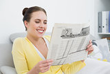 Smiling woman reading newspaper on sofa at home