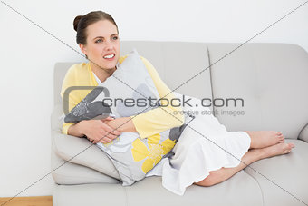 Thoughtful young woman relaxing on sofa