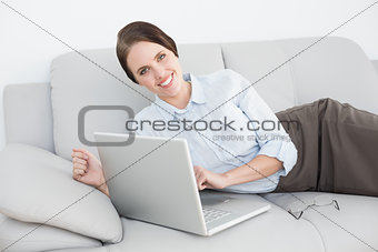 Portrait of a smiling well dressed woman using laptop on sofa