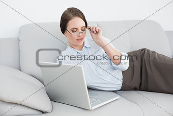 Smartly dressed woman using laptop on sofa