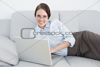 Smartly dressed smiling woman with laptop on sofa