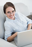 Portrait of a smartly dressed woman with laptop on sofa