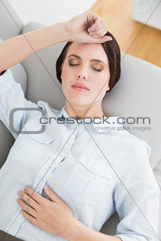 Well dressed young woman resting on sofa