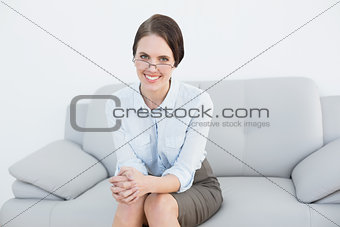 Portrait of a smiling smart woman sitting on sofa