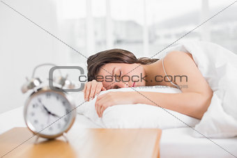 Woman sleeping in bed with alarm clock in foreground