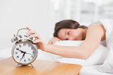 Blurred woman in bed extending hand to alarm clock