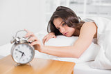 Woman in bed extending hand to alarm clock