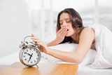 Woman yawning while extending hand to alarm clock