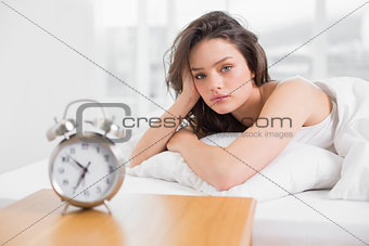 Beautiful woman in bed with alarm clock on bedside table