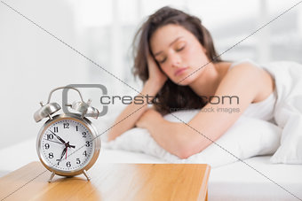 Sleepy woman with alarm clock in foreground