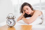 Sleepy woman looking at alarm clock on bedside table